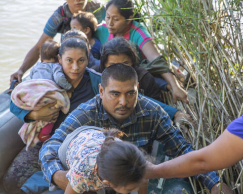 Migrants cross the Rio Grande